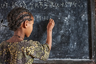 Girl writing out mathematical equations on a blackboard.