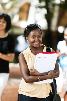 Smiling girl holding a binder.