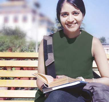 Smiling girl sitting on a park bench, holding an open book.